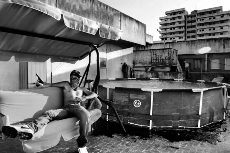 "Naples, Scampia neighborhood, a guy with his gun 7,65 on the top of ""The Sails"" a particular building so called for their shape. © Souvid Datta – Sonagachi: Vanishing Girls"