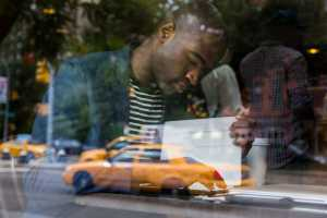 Young Black Man with Digital Tablet in a Cafe. © william87 - Fotolia.com