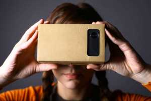 Color shot of a young woman looking through a cardboard, a device with which one can experience virtual reality on a mobile phone. © bizoo_n - Fotolia.com