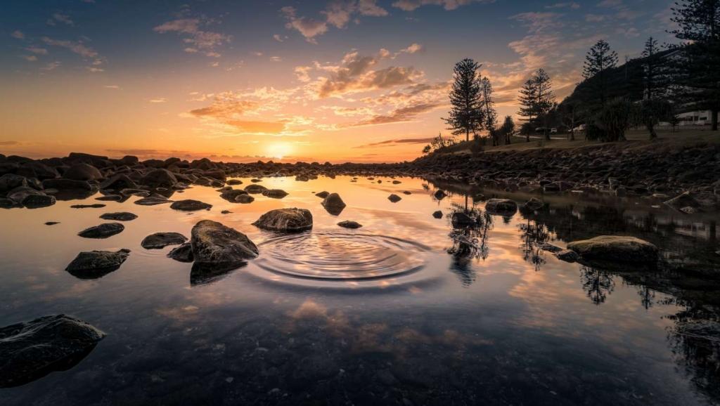Zahlreiche Bildzutaten: Wasser, Felsen, Sonne, Ufer und ein Steinchen.